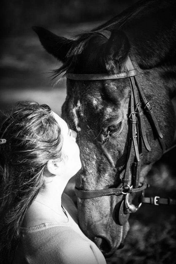 girl kissing horse portrait